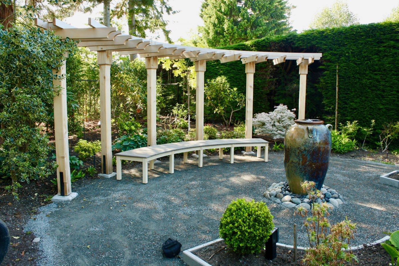 Curved garden bench under arbour