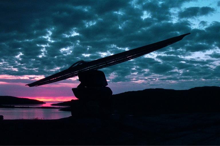 Netsilikmeot kayak on inukshuk at sunset